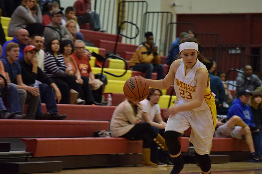 Abriana Burr, 12, dribbles towards the net and the end of her high school basketball career.