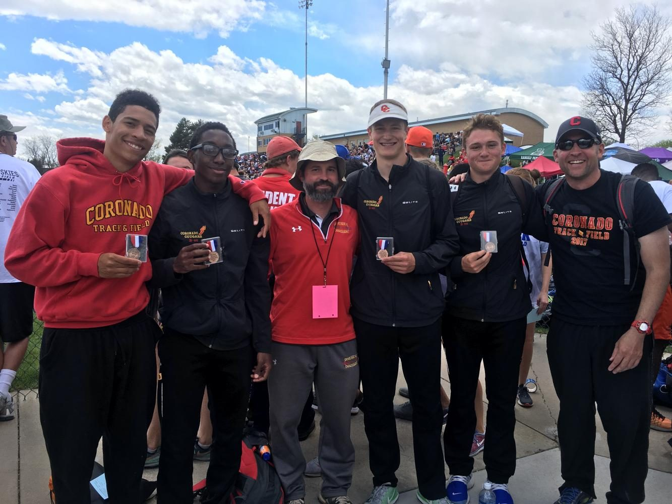 Head Coach Kane, along with Coach Stoughton, pose with the state medalist school record holding boys 4x100 meter relay at the State Track and Field Championships.