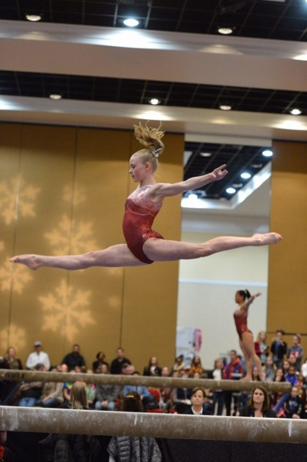 Lauren Gryboski soars above the beam at a competition.