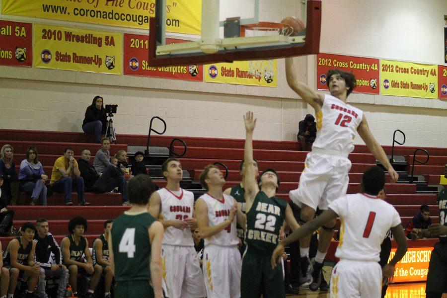 Jareth Morey dunks while his teammates look on.