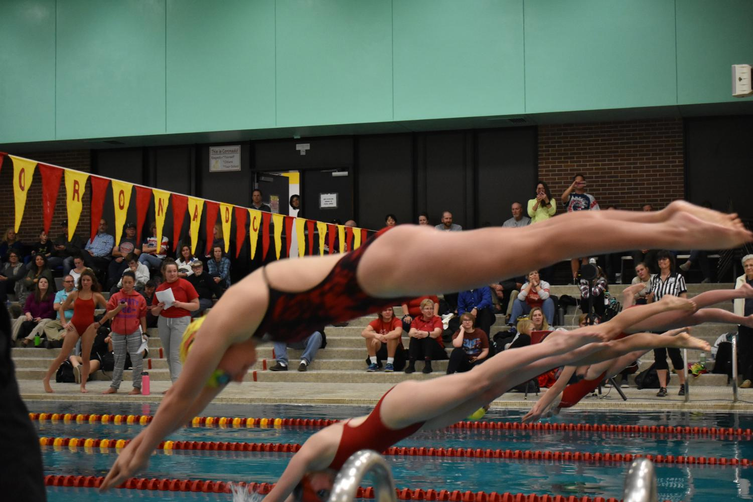 A Liberty swimmer and a Coronado swimmer dive off the blocks at the start of their race.