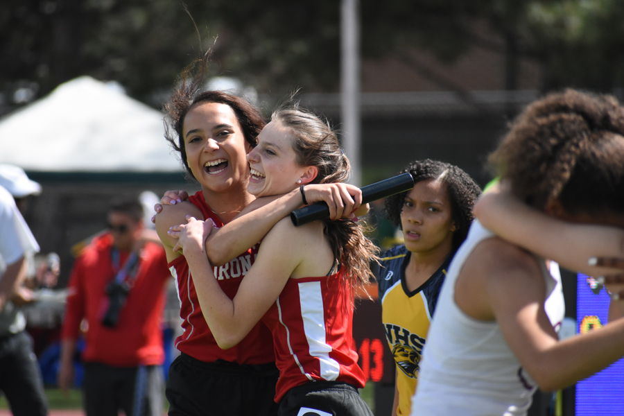 Jasmyne Terrones celebrates with Alison Ambuul after the girls' 4x100 relay took 4th at the State Championships and set a new school record, along with Tinah Muhammad and Janae Israel.